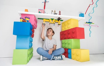 Image of a child playing lego in a cubby
